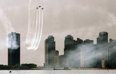The skyline is shrouded in smoke from aircraft being flown through aerobatic maneuvers over Lake Michigan on the Chicago waterfront. The performance was part of rehearsals for the weekends air and water show.