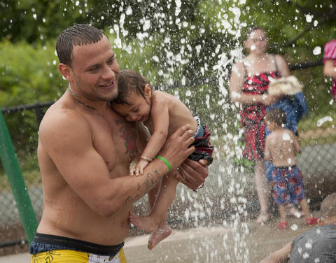 Phillip Ortiz of Allentown, cools off with daughter Mia Mor Ortiz, 1, during the afternoon heat at the Buck Boyle Park water park on Tuesday.