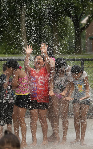 Josseline Olivares, 10, of Quakertown (center), cools off with a group of kids brave a large spray of water as they cool off from the afternoon heat at the Buck Boyle Park water park on Tuesday.