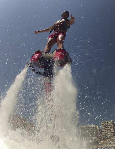 A boy practices flyboarding at the beach of Magaluf, in Palma de Mallorca, one of the Spanish Balearic islands, August 22, 2013. The Flyboard is an ingenious invention which consists of a board fitted with shoes that the user wears and is attached to a watercraft on the other end that powers up the board to propel the user upwards into the air and dive in and out of the water. Flyboarding is inspired from a mix of extreme sports such as jet-skiing, snowboarding and acrobatic diving. REUTERS/Enrique Calvo.