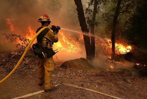 A firefighter from Ebbetts Pass Fire District uses a hose to cool down hot spots of back fire as he battles the Rim Fire on August 21, 2013 in Groveland, California. The Rim Fire continues to burn out of control and threatens 2,500 homes outside of Yosemite National Park. Over 400 firefighters are battling the blaze that is only 5 percent contained.