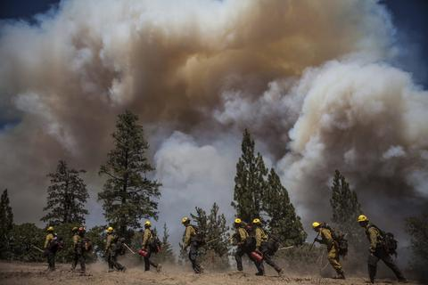 Los Angeles County firefighters hike in on a fire line on the Rim Fire near Groveland, California, August 22, 2013. The wildfire raging out of control near Yosemite National Park in northern California ballooned to nearly 54,000 acres on Thursday, more than tripling in size from the day before, forest officials said. REUTERS/Max Whittaker