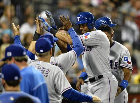 The Rangers' Alex Rios is congratulated in the dugout by his teammates after hitting a two-run home run that scored A.J. Pierzynski during the sixth inning.