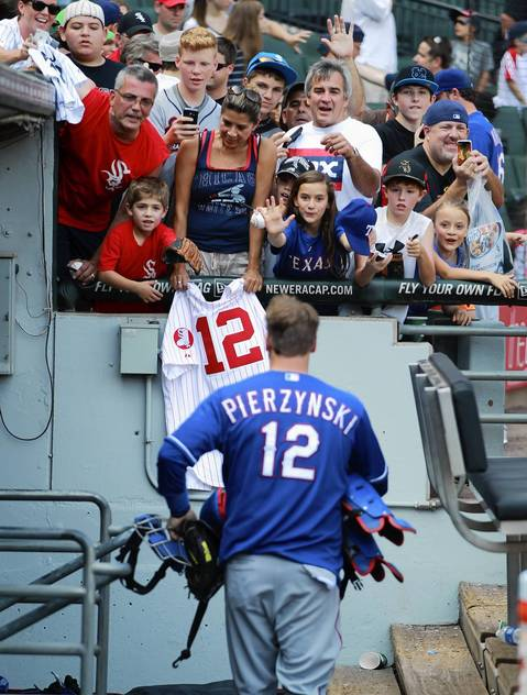 Sox fans try to get an autograph from the Rangers' A.J. Pierzynski after Sox's 5-2 win.