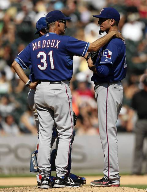 Rangers starter Matt Garza listens to pitching coach Mike Maddux in the 6th inning.