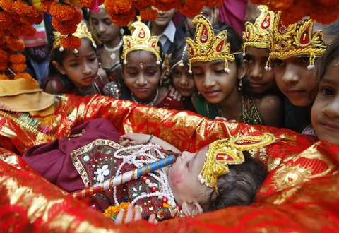 Schoolgirls dressed as Radha, the consort of Hindu Lord Krishna, look at a child dressed as Krishna during the celebrations to mark Janmashtami festival in the western Indian city of Ahmedabad August 27, 2013. The festival, which marks the birth anniversary of Lord Krishna, will be celebrated across India on Wednesday.