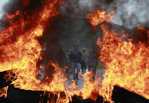 Farmers stand in front a burning tyre barricade during a protest against the government in the municipality of Ventaquemada, near Tunja August 26, 2013. The demonstrations, which began last week, are the second wave of so-called national strikes against Colombia's President Juan Manuel Santos' agriculture and economic policies which farmers say leave them unable to make any profit.