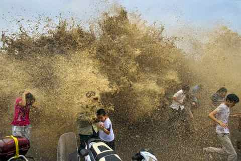 Visitors run away from waves from a tidal bore as it surges past a barrier on the banks of Qiantang River, in Hangzhou Zhejiang province.