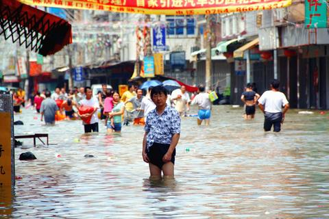 Residents wade in a flooded street in Shantou, China. 20 people were killed and 7 others missing after typhoon Utor made landfall in Guangdong province.