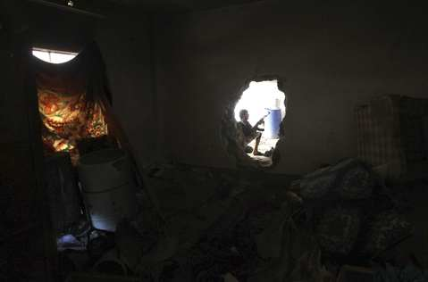 A Free Syrian Army fighter is seen through a hole in a wall in Deir al-Zor August 26, 2013. Picture taken August 26.