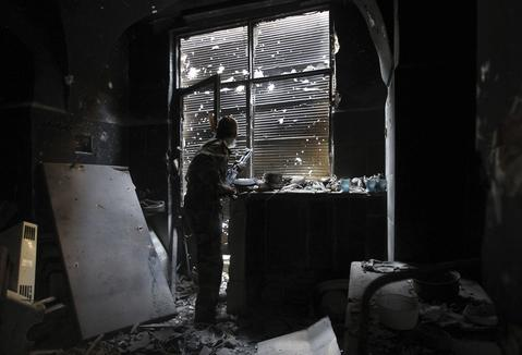 A Free Syrian Army fighter looks outside while holding his weapon as he takes cover inside a damaged shop in the old city of Aleppo August 27, 2013.