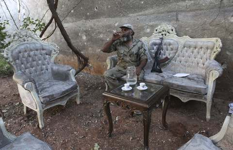 A Free Syrian Army fighter drinks water as he sits on a sofa in the old city of Aleppo August 27, 2013.