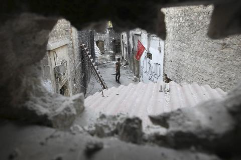A Free Syrian Army is pictured through a hole in the old city of Aleppo August 27, 2013.