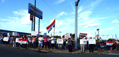 Members of the Syrian American Society protest U.S. involvement in Syria. They are at the inetersection of MacArthur Road and Grape Street.