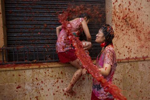 "Revellers take part in the annual ""Tomatina"" festivities in Bunol, near Valencia, on August 28, 2013. Twenty thousands revellers hurled 130 tonnes of squashed tomatoes at each other, drenching the streets in red in a gigantic Spanish food fight known as the Tomatina."