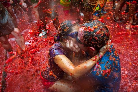 Two Revellers kiss each other covered in tomato pulp while participating the annual Tomatina festival on August 28, 2013 in Bunol, Spain. An estimated 20,000 people threw 130 tons of ripe tomatoes in the world's biggest tomato fight held annually in this Spanish Mediterranean town.