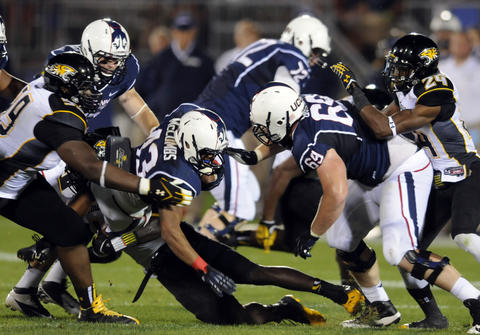 Lyle McCombs carries the ball in the fourth quarter against Towson University at Rentschler Field. UConn lost, 33-18.