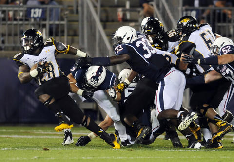 Towson's Terrence West breaks a tackle and runs in to score in the fourth quarter against UConn at Rentschler Field. UConn lost, 33-18.