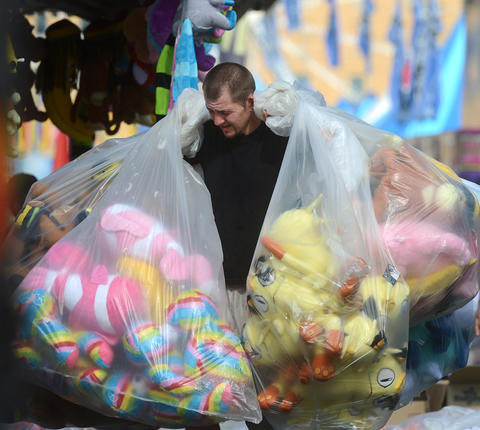 Mark Jablon an employee from A.B. Concessions, carries bags of stuffed animals as they prepare for opening day at The Great Allentown Fair Tuesday.