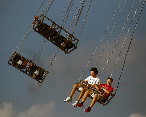 Max Purshock, left, and Quentin Sowers, both of Allentown, ride the swings during the Great Allentown Fair Thursday August 29, 2013.