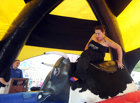 Jay Navarre of Allentown tries to stay on the Bull ride during The Great Allentown Fair Friday.