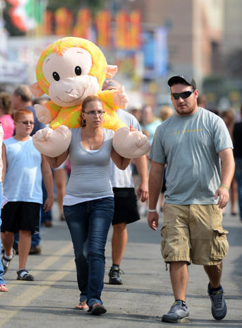 Sara Wysocky of Palmerton (left) carries a large monkey that Derek George of Palmerton (right) won at The Great Allentown Fair Friday.