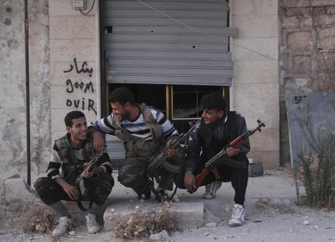 Free Syrian Army fighters react as they sit together along a street in Kansafra in Idlib province September 3, 2013.