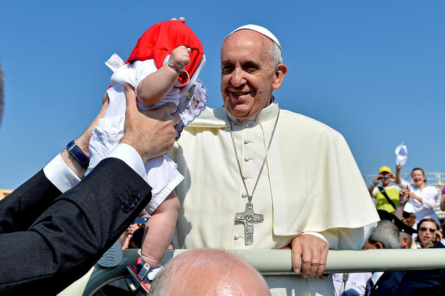Pope Francis blesses a child as he arrives on Lampedusa, Italy. Francis celebrated Mass on the pier with a group of immigrants.