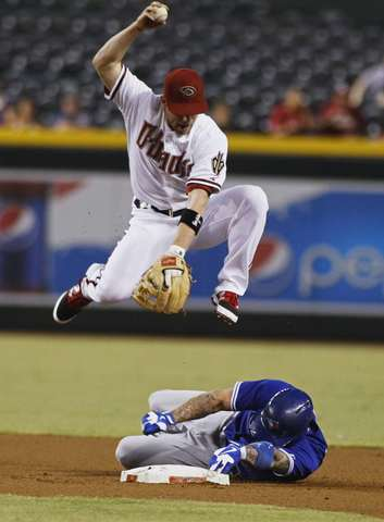 Arizona Diamondbacks second baseman Aaron Hill leaps to avoid the slide of Toronto Blue Jays' Brett Lawrie who breaks up a double play during the first inning of their MLB interleague game in Phoenix, Arizona, September 3, 2013.