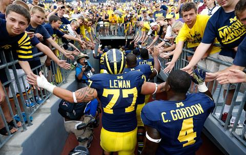 Taylor Lewan #77 and Cameron Gordon #4 of the Michigan Wolverines leave the field after a 59-9 win over the Central Michigan Chippewas at Michigan Stadium on August 31, 2013 in Ann Arbor, Michigan.