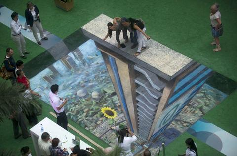People pose around the work of British artist Julian Beever, specialized in pavement drawings, wall murals and realistic paintings, made in a shopping center in Medellin, Antioquia department, Colombia on September 5, 2013. Beever made the painting using colour chalks.