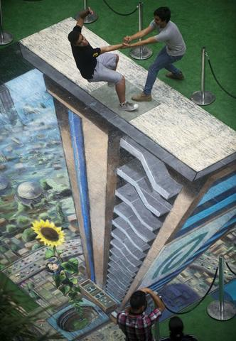 Two men pose by the work of British artist Julian Beever, specialized in pavement drawings, wall murals and realistic paintings, made in a shopping center in Medellin, Antioquia department, Colombia on September 5, 2013. Beever made the painting using colour chalks.