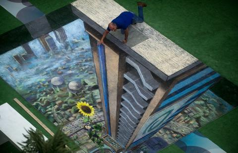 A man poses by the work of British artist Julian Beever, specialized in pavement drawings, wall murals and realistic paintings, made in a shopping center in Medellin, Antioquia department, Colombia on September 5, 2013. Beever made the painting using colour chalks.