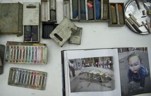 The tools used by British artist Julian Beever,specialized in pavement drawings, wall murals and realistic paintings, as he works on his painting in a shopping center in Medellin, Antioquia department, Colombia on September 4, 2013. Beever is making a painting using colour chalks.