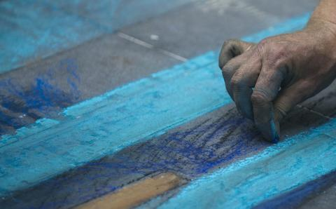 British artist Julian Beever, specialized in pavement drawings, wall murals and realistic paintings, works on his painting  in a shopping center in Medellin, Antioquia department, Colombia on September 4, 2013. Beever is making the painting using colour chalks.