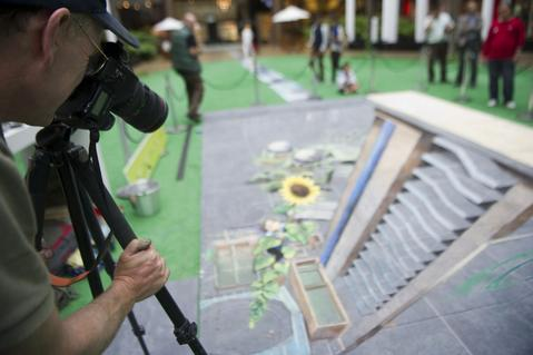 British artist Julian Beever, specialized in pavement drawings, wall murals and realistic paintings, works on his painting  in a shopping center in Medellin, Antioquia department, Colombia on September 3, 2013. Beever is making the painting using colour chalks.