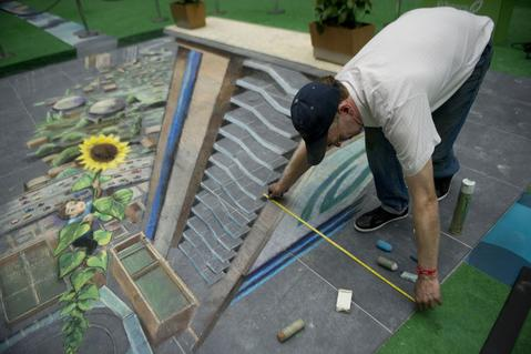 British artist Julian Beever, specialized in pavement drawings, wall murals and realistic paintings, works on his painting in a shopping center in Medellin, Antioquia department, Colombia on September 4, 2013. Beever is making a painting using colour chalks.