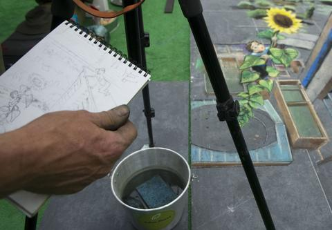 British artist Julian Beever, specialized in pavement drawings, wall murals and realistic paintings, carries a sketch of his painting in a shopping center in Medellin, Antioquia department, Colombia on September 4, 2013. Beever is making a painting with colour chalks.