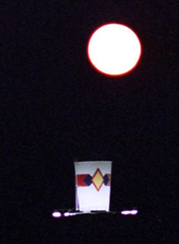 The full moon rises above the former Dixie cup atop the Wilson Park complex  in Wilson Monday night.
