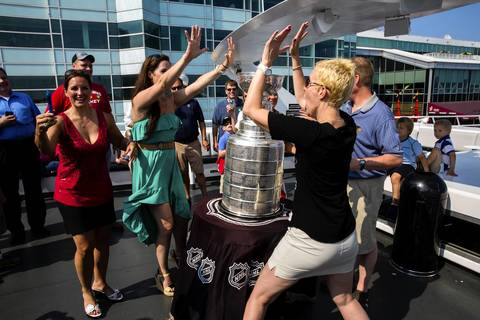 Whitney Parchman, right, celebrates with Rhonda McClelland, left, and Gale Freis in front of The Stanley Cup on board the Anita D II at Navy Pier. The Cup was brought to a private party by her husband Troy Parchman, an equipment manager for the Chicago Blackhawks.