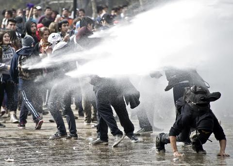 Students clash with riot police during a protest to demand Chilean President Sebastian Pinera's government an intensive educational reform and to break with other legacies of the dictatorship of Augusto Pinochet (1973-1990), in Santiago, on September 5, 2013.