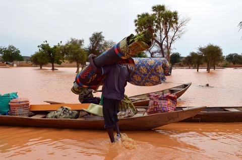 A man carries his belongings into a pirogue on September 5, 2013 in a district in Niamey where floods caused 26 casualities and affected 75,347 people and 13,000 hectares of farmland with damages estimated to 32 billion francs CFA (48.8 million euros), according to a statement.