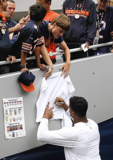 Chicago Bears defensive end Corey Wootton signs gear for fans before the Bears season opener at Soldier Field on Sept. 8.