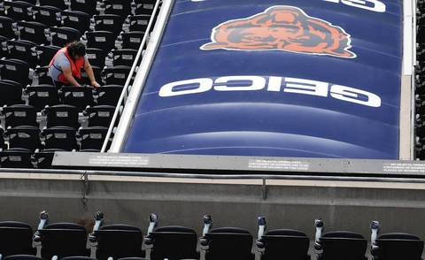 A member of the cleaning crew wipes down seats at Soldier Field on Sept. 8