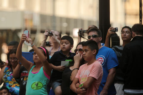 "Pedestrians photograph a crew filming scenes from the upcoming film ""Transformers 4"" on LaSalle Street in Chicago."