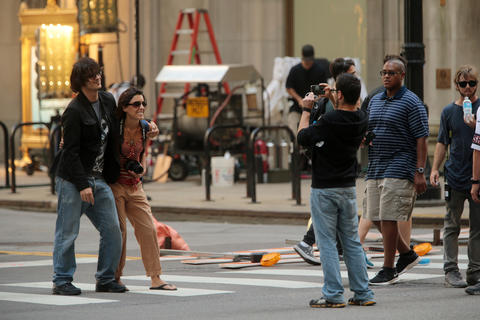 "A couple gets their photo taken between takes as a crew filmed scenes from the upcoming film ""Transformers 4"" on LaSalle Street in Chicago."