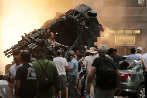 "A crew pauses between filming scenes from the upcoming film ""Transformers 4"" on LaSalle Street in Chicago."