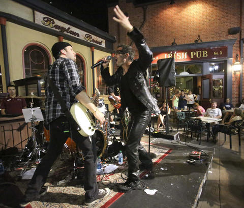 The U2 tribute band 'Elevation,' from Toronto, Canada, performs at the 2nd Annual Great Irish Hooley, at Raglan Road Irish Pub at Downtown Disney, Sunday, September 1, 2013. From left, lead guitarist Kevin Strom (as The Edge) interacts with Shawn Brady (as Bono). They are scheduled to be back at Downtown Disney for a series of St. Patrick's Day concerts in March, 2014. Since 2002, Elevation has toured worldwide in 187 cities, including performances in Japan, Italy, Germany, Austria, Bosnia, Trinidad and the Dominican Republic.  It's their 11th year performing at Walt Disney World. (Joe Burbank/Orlando Sentinel) B583163982Z.1 ..