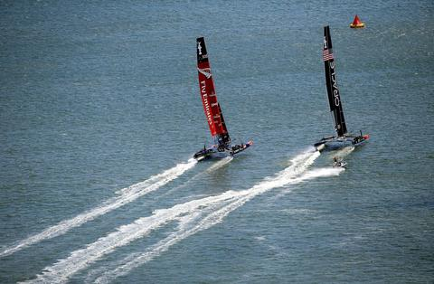 Oracle Team USA and Emirates Team New Zealand race side-by-side as they approach the start of race 5 of the America's Cup Finals on September 10, 2013 in San Francisco, California.