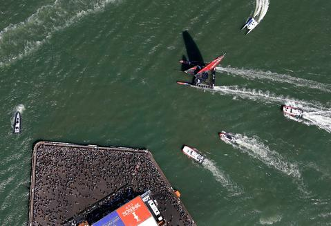 Emirates Team Zew Zealand passes spectators watching from a pier at America's Cup Park during race 5 of the America's Cup Finals against Oracle Team USA on September 10, 2013 in San Francisco, California.